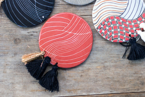 Ceramic Tassel Coaster Set by Maya Loom. Handmade in Guatemala. Hand painted mismatched round ceramic coasters, featuring contrast three tassel detail. Set of 4. Color multi.