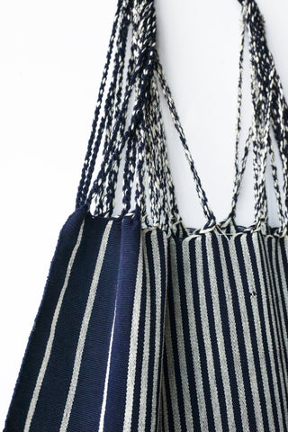 Navy Hammock Bag by The Global Trunk. Handwoven in Mexico. These little tote bags are perfect for going to the market or the beach! Each Hammock Bag is handwoven on a back-strap loom by artisans in the highland region of Chiapas, Mexico. Color navy. 100% cotton.