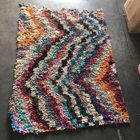 Newman Boucherouite Rug by Atelier Boemia. Handcrafted in Morocco. This Boucherouite Rug is a genuine article produced by women in the areas around Marrakesh and in the Atlas Mountains. These are mostly vintage pieces whose humble beginnings as fabric scraps are turned in to beautiful works of art. One of a kind. Color multi.