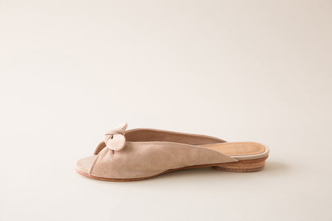 "Huma Blanco Spring 2018 Nolita Mule. Knotted suede strap provides an impeccable finish for this handcrafted open toe mule slide sandal. Open toe slide in soft suede with bowtie detail. Feminine and easy to style with everything from dresses to denim. Made by hand in Peru. Color nude. Suede upper, leather insole, leather lining, leather sole, and wood heel with rubber sole. Leather insole with leather heel. Heel height: 0.5"". Sizes 37 38 39."