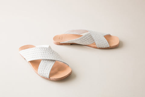 Huma Blanco Spring 2018 Odessa Slide in White. Wide crisscrossed straps fashioned in genuine pony calf hair lend chic texture and visual intrigue to a handmade slide sandal. Color white. Calf hair upper, leather insole, leather lining, leather sole, and wood heel with leather sole. Sizes 37 38 39.