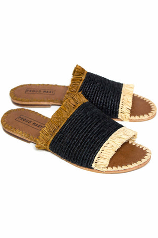 Accompany Exclusive Proud Mary Raffia Fringe Slide in Desert. Crocheted woven raffia featuring ivory and brown fringe and contrast side stitching. Handcrafted in Morocco. Classic slide silhouette with fringe detail on upper and hand stitched leather sole. Raffia upper. Leather sole. Rubber grip at heel. Color black brown white. 100% raffia, leather. Sizes 6 7 8 9 10 11.
