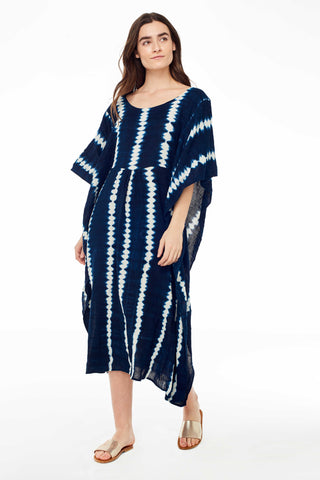 Proud Mary Indigo Shibori Caftan. Shibori dyed caftan made by a woman's cooperative in Mali using locally sourced Indigo. Flowy silhouette made from organic cotton voile. Dyed with locally harvested indigo. Wide boatneck. Long flutter sleeves. Handmade by artisans in Mali. Measures 52 inches from shoulder to hem. Color indigo white. 100% cotton. One size fits most.