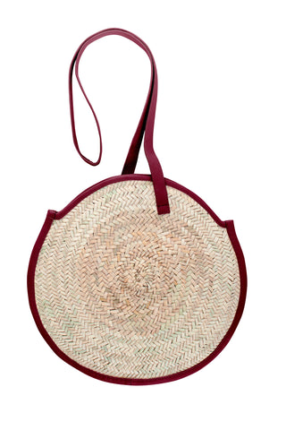 Parme Marin Spring 2018 Tadlak Shoulder Bag in Crimson. Circular palm leaf and leather trimmed purse, lined inside with inside pocket. Measures 15 inches across. 22 inch strap drop. Color burgundy. Woven palm leaf with leather trim. One size