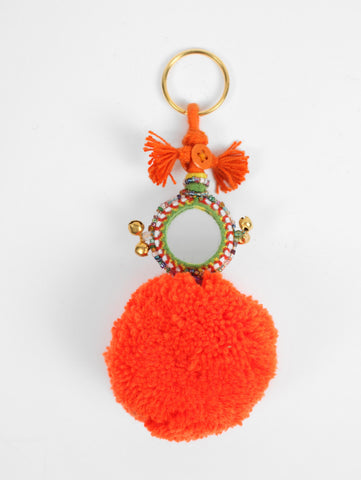 "The Pom Pom Mirror Keyring by Bohemia Design is a bright wool pom pom embellished with colorful decorated mirrors, beads and bells -- handmade in India by artisans. This eye-catching pom pom keyring adds a fun twist to your everyday routine. Available in Navy Jade Green Purple Red Yellow Orange Pink Ivory Grey Azure Black  100% Wool Pom Pom Measurements 6"" L"