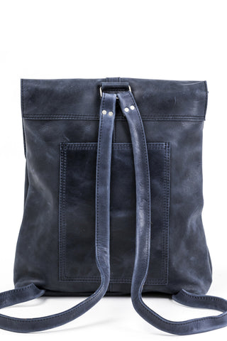 Raven and Lily Yami Leather Backpack in Navy. This locally-sourced Ethiopian leather backpack is a must-have everyday accessory. Small inside pocket. Magnetic closure under the flap. Two thin leather straps. Leather tassel detail. Unlined vegetable dyed leather. Handmade by women in Ethiopia. Color navy blue. 100% leather. Measures 12.5 inches by 11 inches. 4 inch gusset. 27 inch straps. One size.
