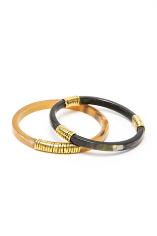 Raven and Lily Spring 2018 Kerina Horn & Brass Bangles. Classic and elegant bangle set made with horn and wrapped with brass. Set of two upcycled horn and brass bracelets. Hand carved recycled horn. Polished brass wrap detail. 2.75 inch diameter. Color black natural gold. Horn, brass. One size fits most.