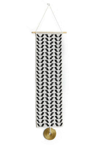 Chevron Beaded Wall Hanging by Sidai Designs. Handmade in Tanzania. Glass beaded wall hanging with a single large brass disk. The beaded panel is handwoven together with recycled grain sacks onto a wooden dowel. Color black and white.