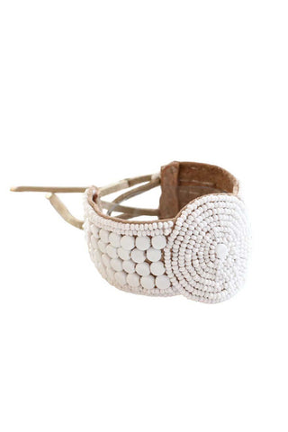 Sidai Designs Spring 2018 Beaded Leather Disc Cuff Bracelet. Suede highly adorned with white glass beads. Soft leather lace closure with adjustable sterling silver fastening. Inspired by the jewelry worn by the Sipolio warriors. Handmade in Tanzania. 1 inch width. Color white. Suede base. Glass beads. Adjustable size.