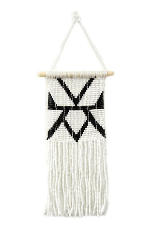 Rhombus Beaded Wall Hanging by Sidai Designs. Handmade in Tanzania. Glass beaded wall hanging with a beaded fringe finish. The beaded panel is handwoven together with recycled grain sacks onto a wooden dowel. Color black and white.