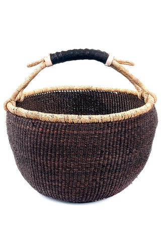 Ghanaian Bolga Basket by Swahili Modern. Handwoven in Ghana. This beautifully woven basket is made using durable elephant grass. Each basket features a contrasting rim and handle that is wrapped with soft, hand-dyed cow leather. Color brown. 100% elephant grass.