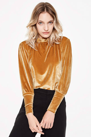 Sitting Pretty Fall 2018 Mia Ruffle High Neck Top in Gold. Long sleeved high neck velvet top featuring ruffle collar and wide fitted cuffs. Gathered shoulders. Curved hem. Button keyhole back closure. Loose fit. Made in South Africa. Color gold. 100% velvet. Sizes small medium large.