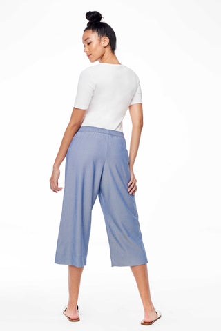 Sitting Pretty Spring 2018 Ellen Culottes in Denim. Loose fitting cotton chambray culotte pant. Wide leg with elastic waistband. Front patch pockets. Cropped pant. Small measures 31.5 inches from waist to hem. No side seam. Unlined. Color denim. 100% cotton. Sizes Small Medium Large.