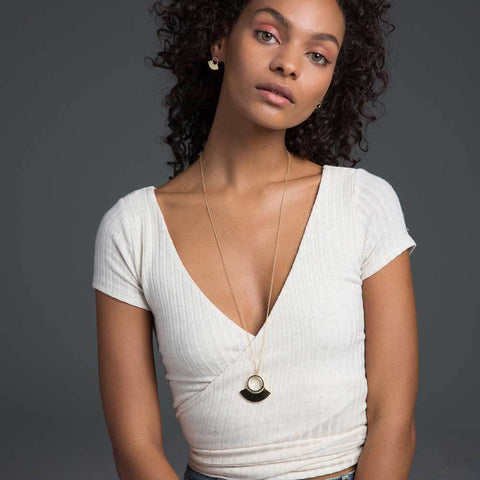 Soko Spring 2018 Petite Paddle Pendant Necklace. Statement pendant necklace featuring polished brass mini paddle pendant. Handcrafted in Kenya using traditional artisan techniques. Color gold. 100% recycled polished brass. One size.
