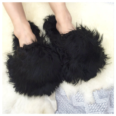 Ariana Bohling Suri Slipper in Black. Slide on baby alpaca slipper made from cruelty free alpaca fur by artisans in Peru. Open toe slipper with Alpaca upper and lining. Micro suede sole. Color black. 100% baby alpaca. Sizes Small Medium Large.