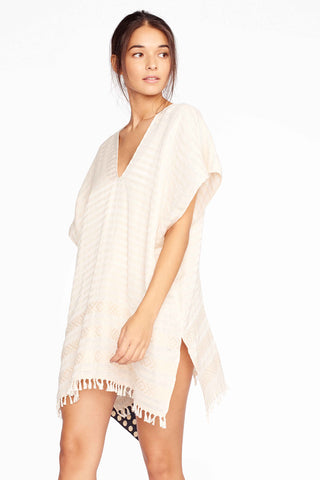 Wax and Cruz XO Caftan in Crema. The XO Caftan is handwoven by master artisans in Mexico. It is an easy piece to throw on over your swim suit at the beach or wear over jeans with sandals. V-neckline with dolman sleeves and side slit at hem. Hand knotted fringe along hem. Measures 34 inches from shoulder to hem. Color natural stripe white. 100% cotton. One size.