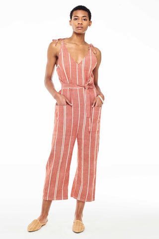Wax and Cruz Spring 2018 Cabiria Jumpsuit in Rust Stripe. Soft handwoven cotton and sexy shoulder ties. V-neckline with removable matching tie wasit belt. Loose fitting with front patch pockets on trouser. Ankle crop. Unlined. Small/Medium measures 50.5 inches from shoulder to hem. Color red and white stripe. 100% cotton. Sizes Small/Medium Medium/Large.