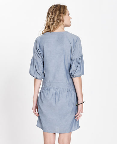 Sitting Pretty Spring 2018 Wangari Dress in Denim. Dropped waist dress with V-neckline and 3/4 length poet sleeves. Mini dress with front and back gathering with curved hem. Relaxed fit. Color Denim. 100% cotton. Sizes Small Medium Large.