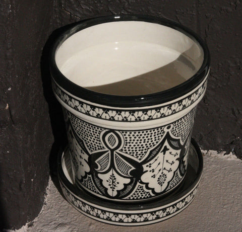 Safi Planter by Atelier Boemia. Hand painted in Morocco. Clever and stylish, each planter has a hole in the bottom for proper drainage and a matching plate to catch any overflow and protect the surface on which the plant stands. Color black and white.