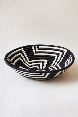 Black and White Geometric Plateau Basket from Indego Africa. Plateau baskets by Indego Africa feature striking colors & traditional motifs. The artisan crafts each one-of-a-kind basket by hand – using needles & fine plant threads made from locally grown sweetgrass. The technique requires patience, precision & great skill to master. These baskets are the best way to add a touch of Rwanda to a coffee table, an office desk, a holiday table or even on your favorite wall.