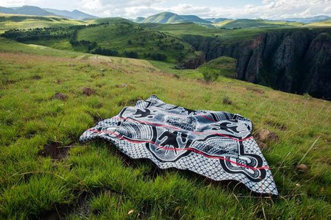 Black Kharetsa Spiral Aloe Basotho Heritage Blanket by Aranda Textiles. Handmade in South Africa. The Basotho heritage blankets are made using a vertical manufacturing process. The 50% wool and 50% Draylon blended yarn is spun in-house, then woven using state-of-the-art jacquard weave technology into the finest quality Basotho blankets. Color black and white.