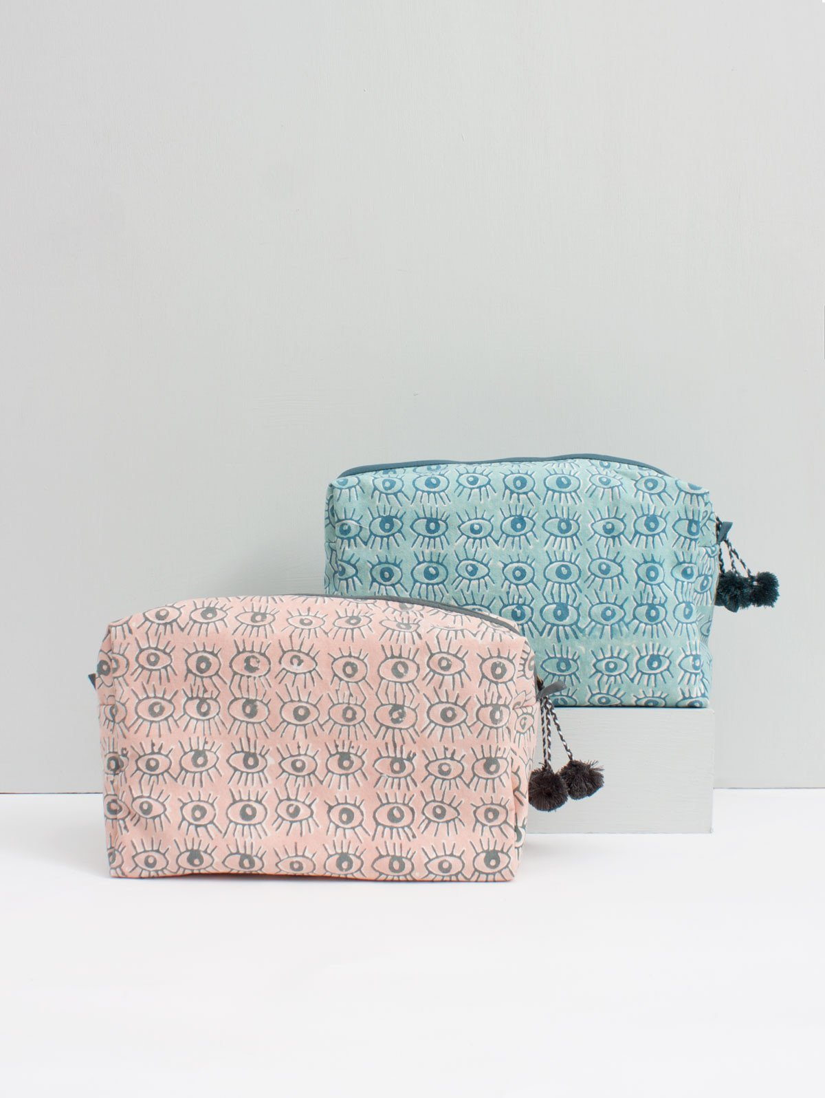 Bohemia Design Eye Print Cosmetic Case. Rectangular gusseted cosmetic bag made from lightweight cotton and finished with tonal pom pom detailing on the zipper. Block printed with evil eye pattern. 10 inches by 6 inches. 4 inch gusset. Colors Blush Duck Blue. 100% Cotton Canvas with Waterproof Lining. One size.