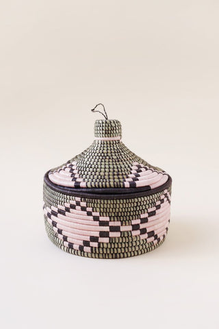 "Marrakech Basket by Indego Africa. Handwoven locally sourced sweetgrass basket featuring black and natural geometric pattern. Perfect for storing small items while adding a touch of bohemian décor to any room. Handwoven locally sourced sweetgrass Available in Pink and White 7"" x 4"""
