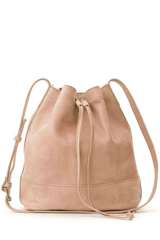 ABLE Tadesse Bucket Bag in Pale Dogwood. Cinch top leather bucket bag with drawstring closure and adjustable strap. Can be worn as shoulder bag or cross body. Minimalist detailing made in soft slouchy leather. Measures 13 inches by 11.5 inches. Color tan. Handcrafted in Ethiopia and Mexico. 100% genuine distressed leather. One size.