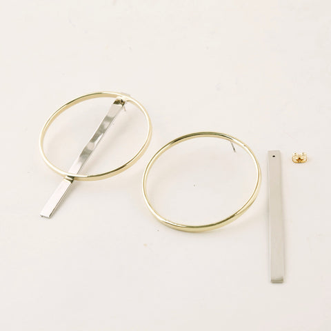 Accompany Exclusive Soko Compass Earring. Jacket hoop earring. Cast brass hoop. Chrome plated silver bar jacket. 2 inch diameter hoop. 3 inch drop from post. Post setting for pierced ears. Color gold silver. Brass, chrome plating. One size.