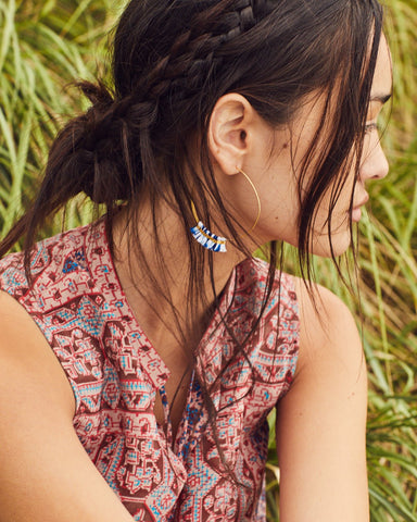 Bluma Project Spring 2018 Fringe Hoop in Blue Ikat. Skinny gold-washed hoops with a row of ikat thread tassels at the bottom. Threader style hoop for pierced ears. Handmade in Guatemala. 2.5 inch diameter. Color blue white gold. Gold plated brass, cotton. One size.