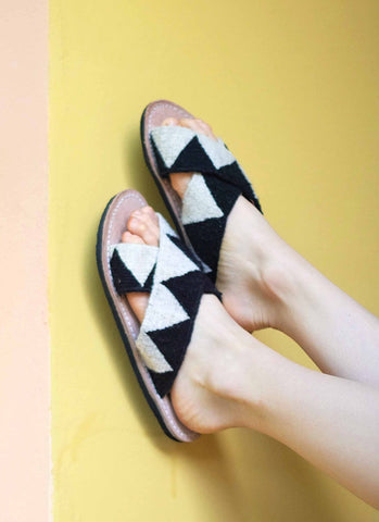 Ilano Jing Slides in Black and White. Handloomed straps made with natural dyes and fibers with leather footbead. Recycled rubber soles. Handmade in Mexico. Sizes 6 7 8 9 10.