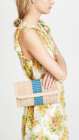 "Bali Cobalt Clutch from Kaanas Spring 2018. This straw KAANAS clutch is a great blend of casual and sophisticated, with a tidy shape and a wide contrast stripe. Fabric: Woven straw. Magnetic closure at front. Lined. Sporty straw bag. Measurements Length: 10.5"" Width: 6"""
