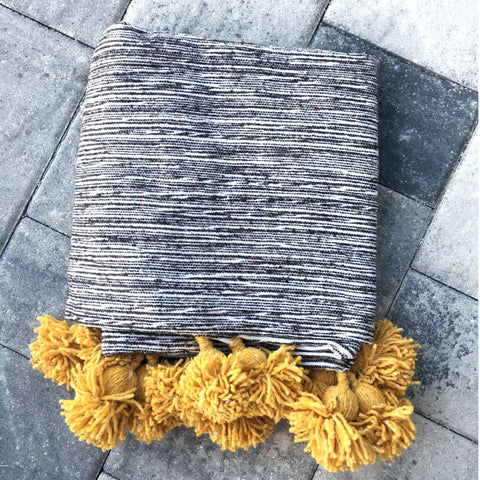 Assia Heather Pom Pom Throw by Atelier Boemia. Handmade in Morocco. Custom-made tassel throw, this beautiful (and cool) blanket makes a fun and functional addition to your bedroom, living space or outdoor fireside lounger. Color grey. 100% cotton.