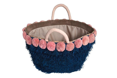 "The Lucca tote by Kayu Spring 2018 features a blue raffia fringe body, pink raffia pom poms and a leather handle. A drawstring lining keeps your belongings safe. Roomy enough for all of your essentials. Measurements 16"" W x 12"" H x 5"" D These fair trade bags are carefully handcrafted by women in the Philippines, Indonesia and Malaysia, preserving their indigenous crafts as well as providing them the opportunity to earn a living wage while working from home and looking after their children."