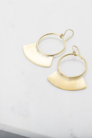 Soko Paddle Earrings. Paddle hoop drop earrings with a fanned silhouette and a subtly antiqued finish. Paddle earrings feature a hand-cast, definitive shape that drops from a hook. Fishhook back for pierced ears. Handmade in Kenya using traditional artisan techniques. 2 inch drop earring. Color gold. 100% recycled brass. One size.