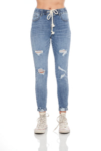 High rise drawstring waist skinny with rolled hem. Medium blue wash with destruction, 5 pocket detailing and off-white drawstring.
