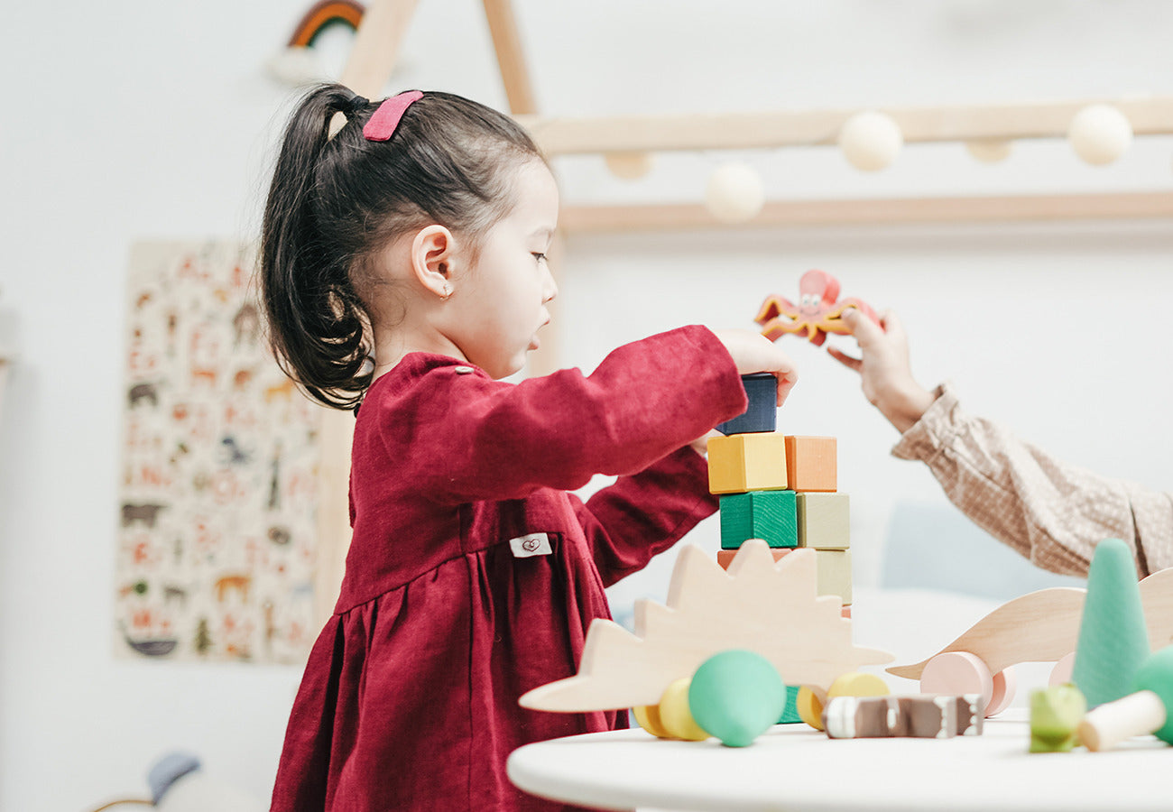 Girl in red dress playing with blocks