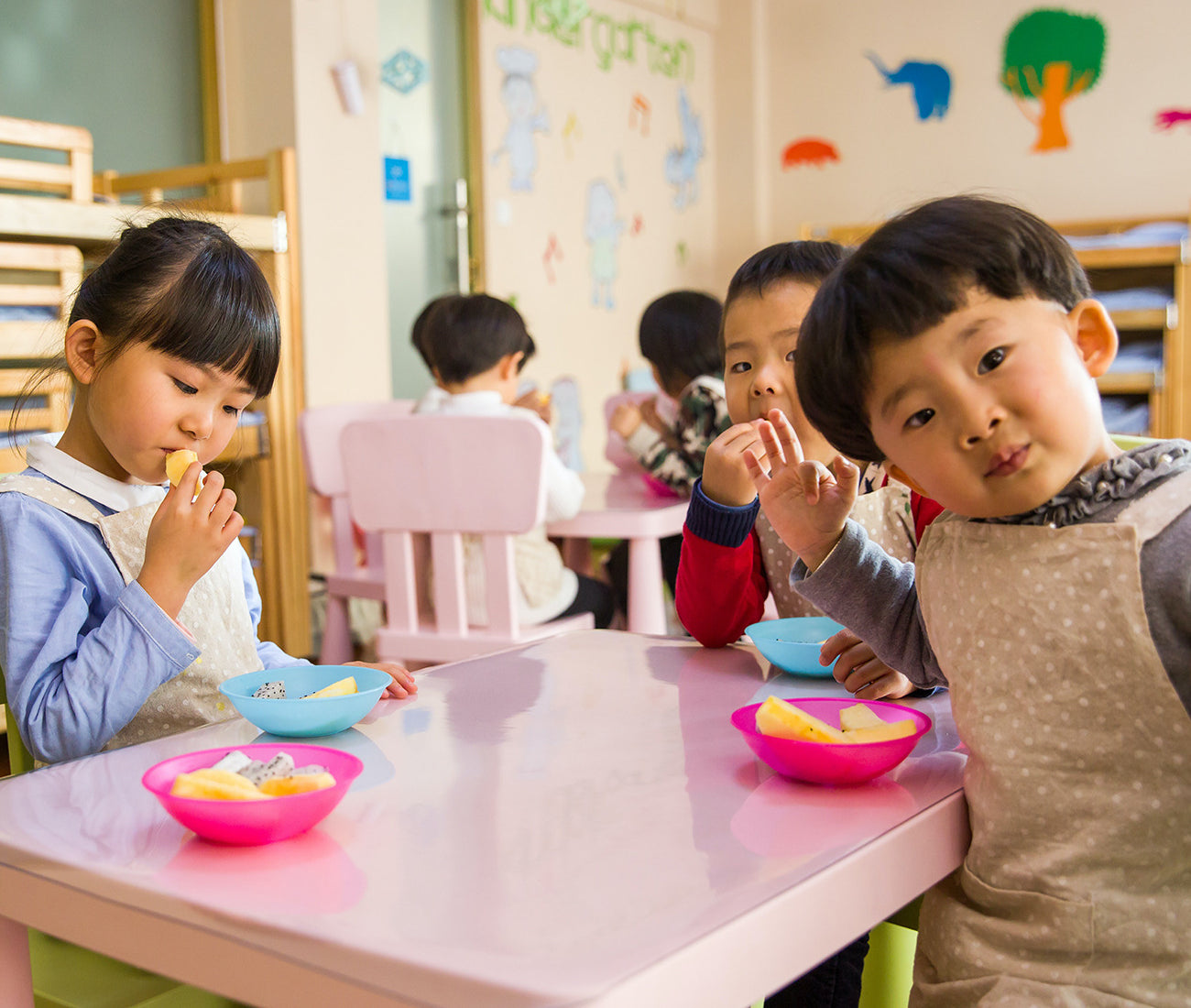 Children at a table, eating snacks