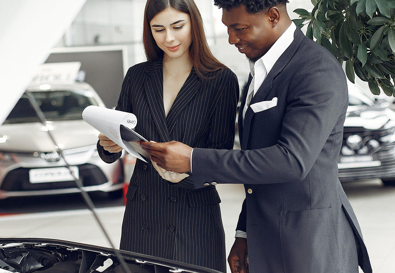 Woman and a man reading papers while looking at cars in a dealership