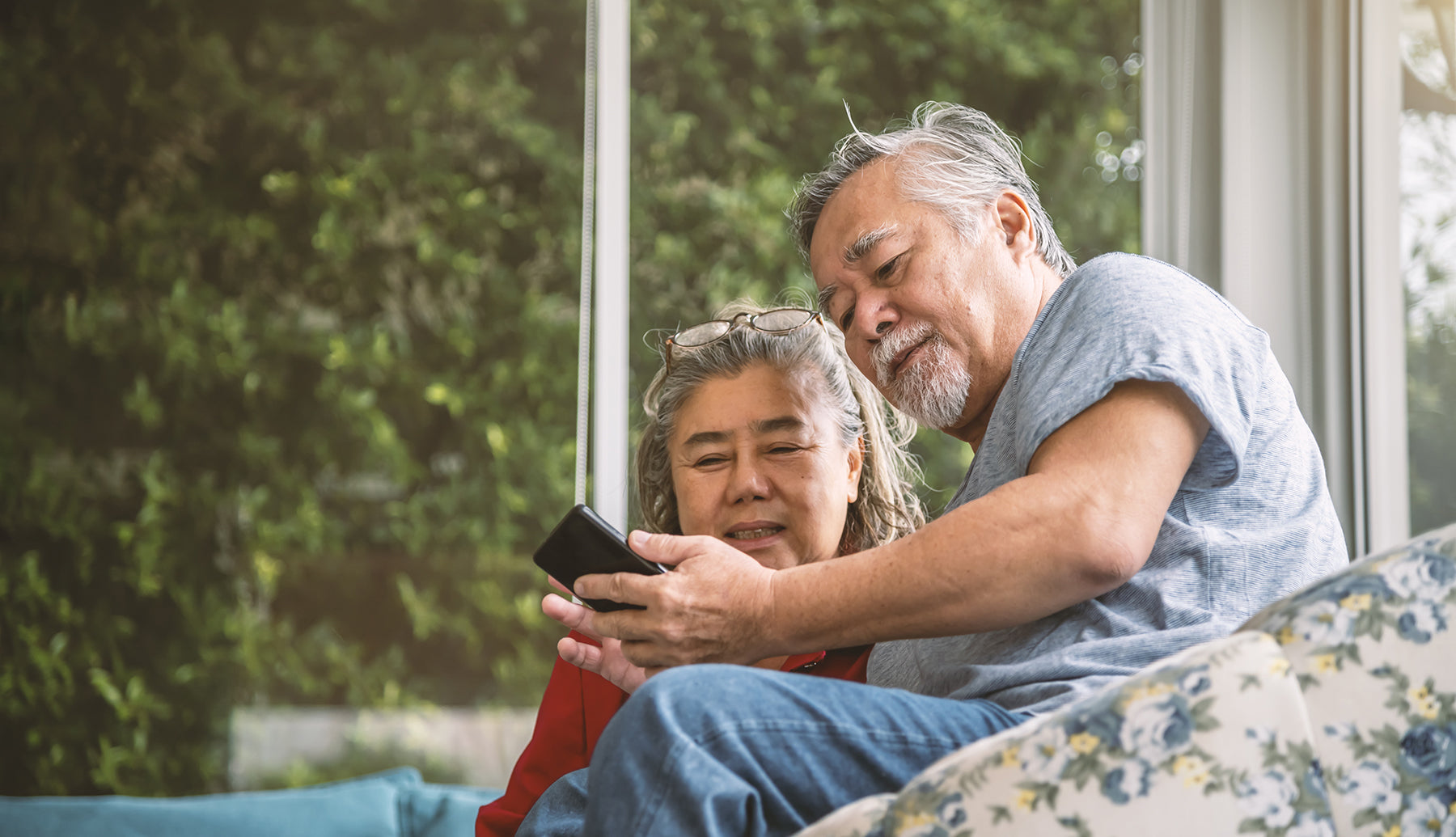 Upper middle aged asian couple on screened in porch looking at smartphone together