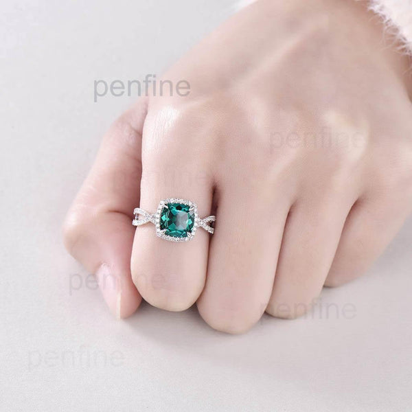 emerald engagement ring in hand