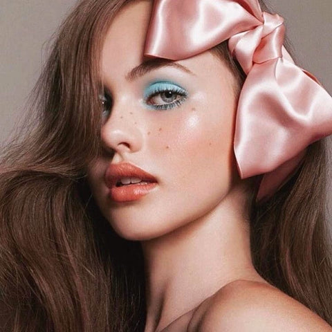 Model with pink satin bow and freckles