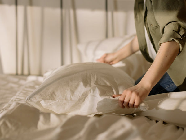 woman removing a pillowcase from a pillow