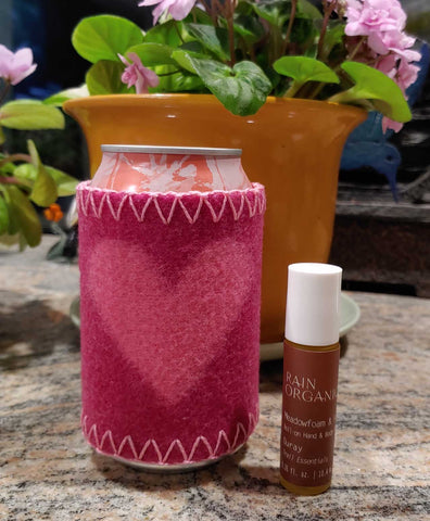 pink Merino wool sleeve coozie for aluminum cans with pink heart and red Ouray rollerball for chapped hands with blooming light pink African violet blooming in background