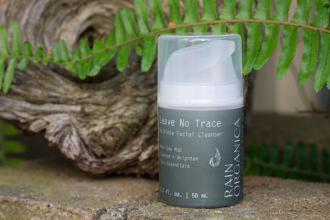 Rain Organica's Leave No Trace Rinse Free Facial Cleanser on a moss covered brick wall with driftwood and ferns behind