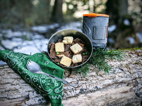 gluten-free mushroom pot pie prepared trailside with a teal green handkerchief and a jetboil shown with a bowl of mushroom pot pie