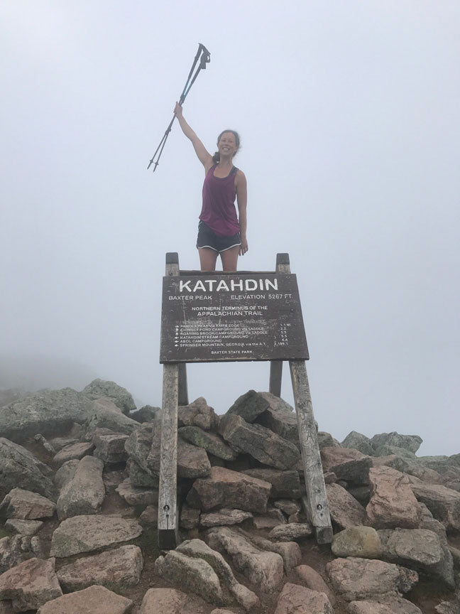 woman at the summit of Mount Katahdin in Maine with trek poles raised in the air in victory amidst clouds and fog