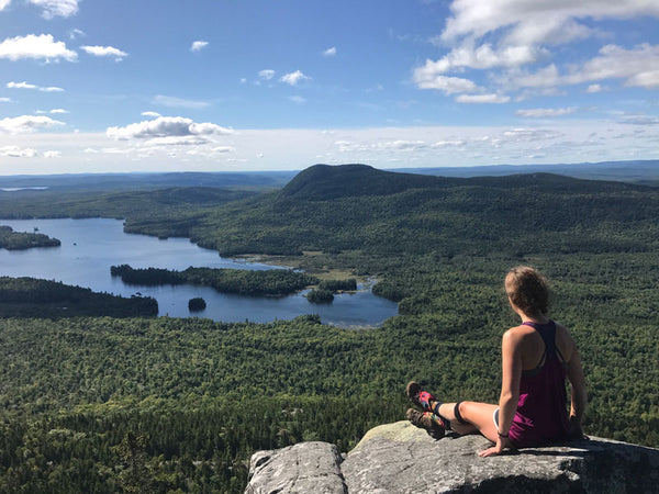 woman enjoys vista views during midday on the Appalachian Trail overlooking lakes from bald mountain tops
