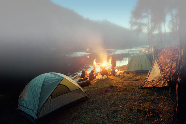people gathered around a campfire next to a river with tents set up