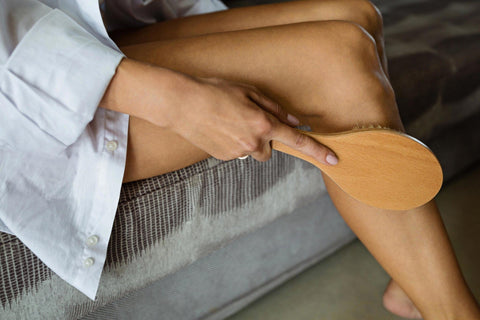 woman dry brushing her legs while sitting on the edge of the bed